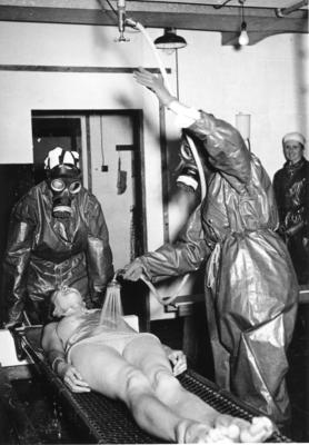 Black and white photograph. Two members dressed in protective clothing and gas masks 'showering' [decontaminating] another member