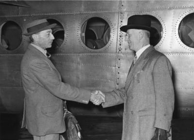 Black and white photograph. Major General Treffry Thompson shakes hands with Air-Marshal Sir Harold Whittingham, medical adviser to the British Red Cross, before his departure to India as British Red Cross commssioner for relief work with refugees in India and Pakistan