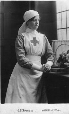 Studio portrait of Florence Egerton in Red Cross uniform with a headveil