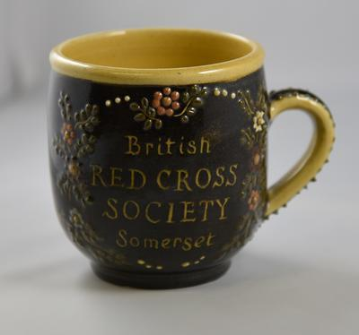 Ceramic slip-decorated mug with inscription 'British Red Cross Society Somerset'