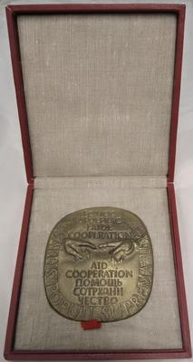 Gold plaque in red presentation box celebrating 'Aid Co-operation.'