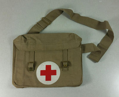 manilla coloured canvas bag with front flap fastening and featuring red cross in white circle to front centre; Meco; Medical Equipment/bag; H/EQP/2002/2
