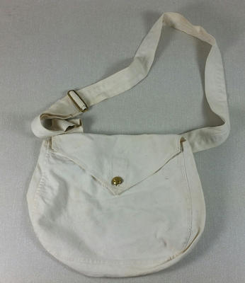 cream coloured canvas bag with front flap fastened by a red cross button