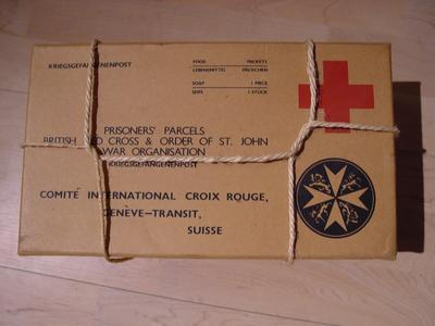 Reproduction Second World War prisoner of war food parcel. Cardboard box featuring the emblems of the British Red Cross Society and the Order of St John with the words 'Prisoners' Parcels, British Red Cross & Order of St John War Organisation'. Part of a collection of items which were never sent but used at the POW Exhibitions which were held during the Second World War.