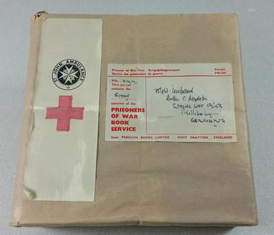 Reproduction Second World War Prisoners of War Book Parcel. Cardboard box covered with brown paper featuring two white labels, one of which contains the emblems of the British Red Cross Society and the Order of St John, the other giving the delivery details. Part of a collection of items which were used at the POW Exhibitions which were held during the Second World War.