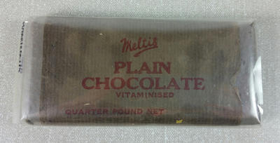 wooden block covered in paper packaging with 'Meltis Plain chocolate' stamped on top