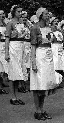 Replica British Red Cross Member's indoor uniform consisting of blue short sleeved dress; white apron with red cross on square bib and two gold safety pins; navy blue belt; white headveil with red cross to front, silver safety pin, gold flat safety pin and two white kirby grips.