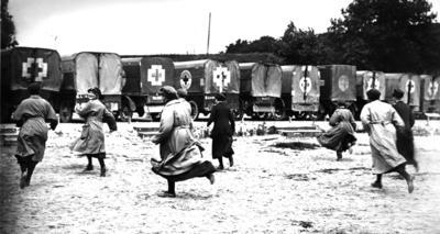 Photograph of female ambulance drivers running to their vehicles in Etaples, France