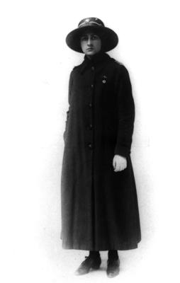 Front view of female member wearing a greatcoat and hat over indoor nursing uniform