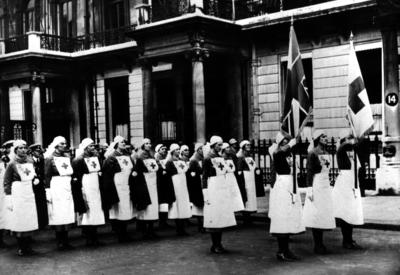 A group of female VADs in indoor uniform assembled outside British Red Cross headquarters in London