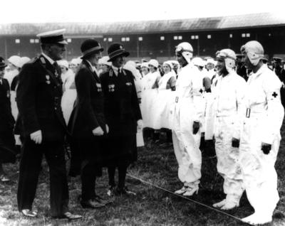 Black and white photograph. HRH Princess Royal, commandant in chief of the British Red Cross, inspecting the Manchester 1st air ambulance detachment. E. Lancs Branch, 1933