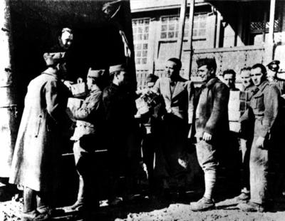 Red Cross parcels being distributed from a vehicle to a group of waiting prisoners of war