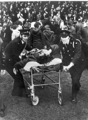 Two male British Red Cross members push a casualty on a stretcher from a football match