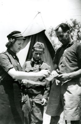 Woman in British Red Cross uniform, with man and boy looking at a message form