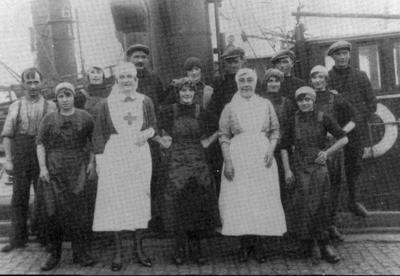 Two Red Cross nurses posing with a group of male and female fisher folk