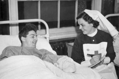 Red Cross nurse writing a letter for a patient at a military hospital