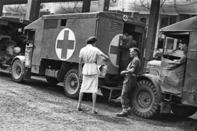 British Red Cross Officer Miss Perry stands by vehicles to distribute gifts