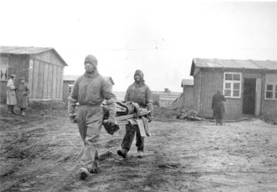Stretcher bearers in Belsen camp clearing the huts