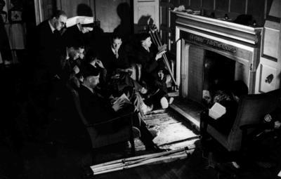 A group of male patients seated around a fireplace at The Grange auxiliary hospital/convalescent home