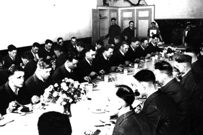 Male patients eating at two long tables, with two nurses in the background serving food, at an auxiliary hospital/convalescent home