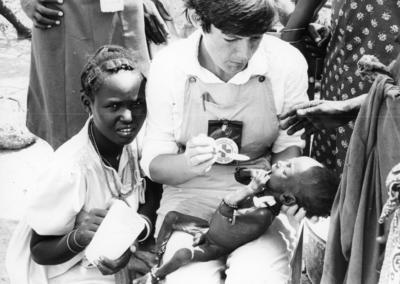 A British Red Cross nurse spoon feeds a Kenyan child as his mother watches on; RCC/5/IN1238