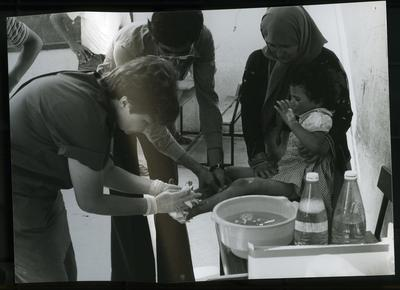 Red Cross personnel attending to a small child's feet in Lebanon; RCC/5/IN1282