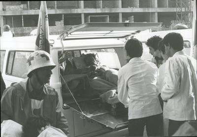 Red Cross medical personnel wearing white coats putting wounded into a Red Cross vehicle with a Red Cross flag for evacuation