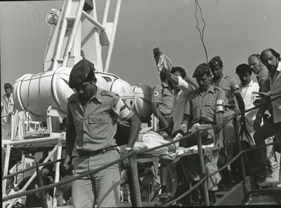 Male Red Cross personnel carrying wounded on a stretcher with a drip down the gangplank from a ship