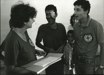 ICRC personnel inform a wounded man with a dressing on his eye that his son has been found and is in Red Cross care