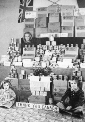"""Jacqueline, Dianne and Jeanette Guise in front of their """"shop"""" made from empty Red Cross parcels and tins"""