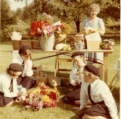 Cadets sitting next to a Flower Arranging Stall at a Fete