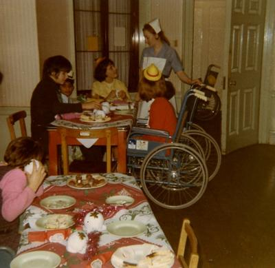 Nurse and Guests at a Christmas Party for Children with Cerebral Palsy