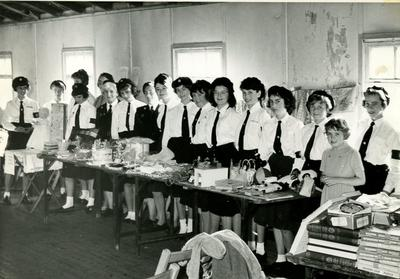 Group of Cadets lined up behind a Stall at a Fair