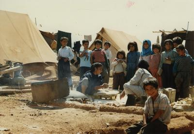 Kurdish children around women cooking in a refugee camp