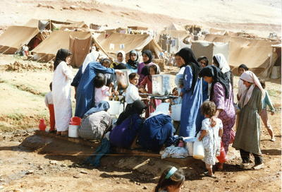Kurdish women and children collecting water at a refugee camp