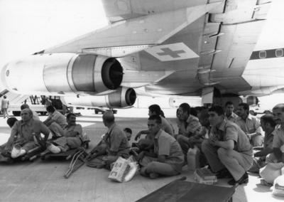 Wounded soldiers seated under a plane with a Red Cross emblem