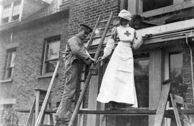 British Red Cross nurse and wounded soldier painting the outside of a hospital