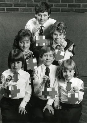 Six youth members in uniform holding 3D emblem style collecting boxes