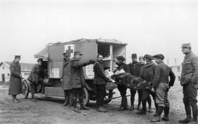 Wounded soldier being loaded into a motorised ambulance