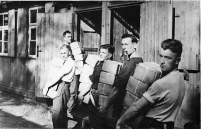 Prisoners of War from Stalag XXA carrying Red Cross food parcels into camp huts