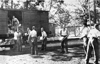 Prisoners of War from Feldpost 31076B unloading Red Cross food parcels from a railway truck; JWO/7/5/IN1844