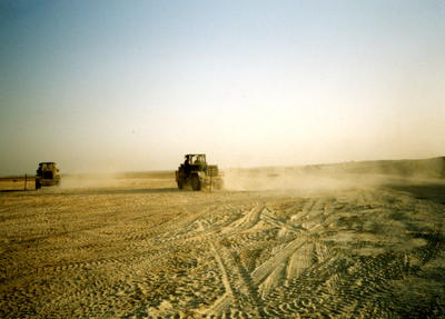 Two JCBs being driven in a desert near 33 General Hospital