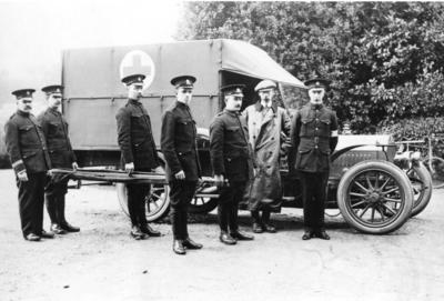 Ambulance bearing Red Cross emblem with British Red Cross members standing alongside