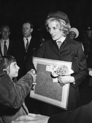 Princess of Wales, in British Red Cross uniform, meets members of the public at a carol service in Bristol