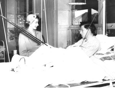Black and white photograph. HRH Princess Elizabeth visiting patient in Red Cross hut for use of tuberculosis patients. At the bedside of a young man.