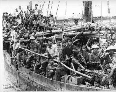 Black and white photograph. A large group of Vietnamese boat people crowded onto a wooden boat in Hong Kong