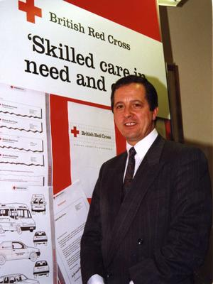 Mike Whitlam standing next to the British Red Cross visual identity handbook exhibition