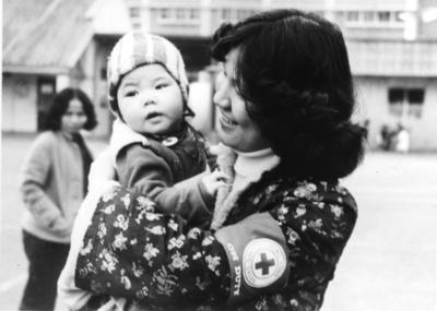 Black and white photograph. Female member of the Hong Kong Red Cross holding up a baby in a refugee camp for Vietnamese boat people