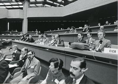 A group of people sitting at benches wearing headphones at a Diplomatic Conference in Geneva