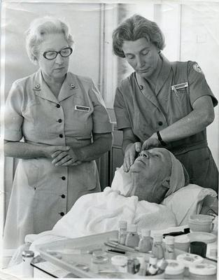Two female British Red Cross beauticians giving a beauty treatment to an elderly woman in Buckinghamshire